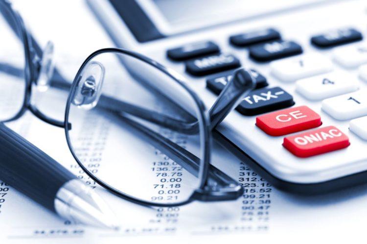 óculos e calculadora sobre uma mesa