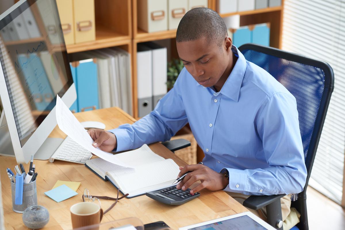 Homem negro de camiseta azul checando relatório em frente ao computador.