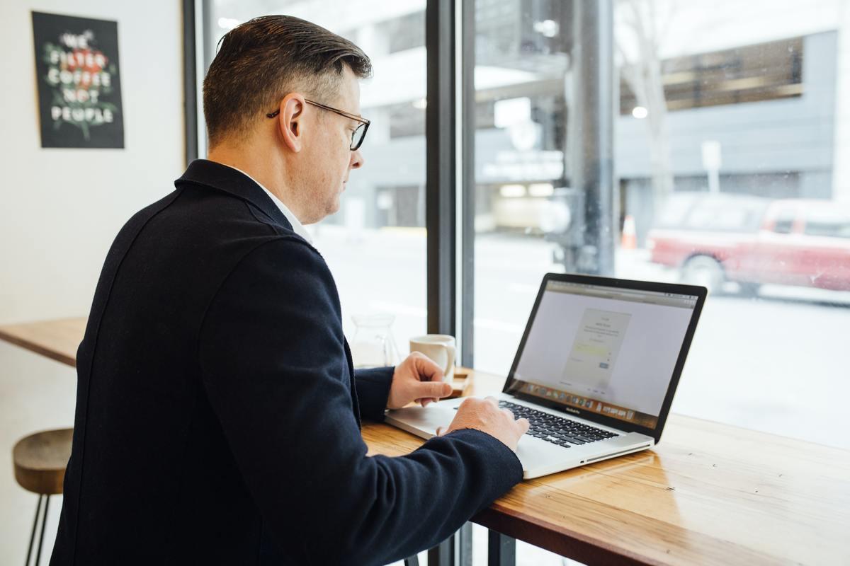 Homem caucasiano de meia idade navega na internet em um notebook apoiado sobre uma bancada de madeira e segura um copo de café.