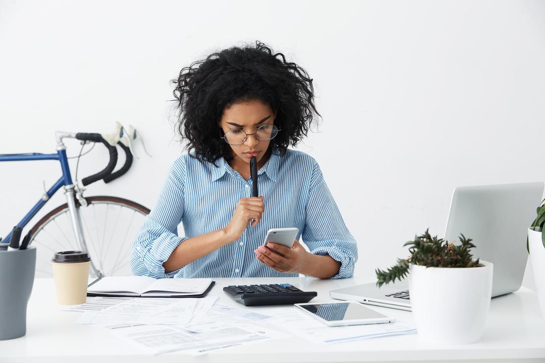 Mulher pensante sentada em uma mesa olhando para o celular
