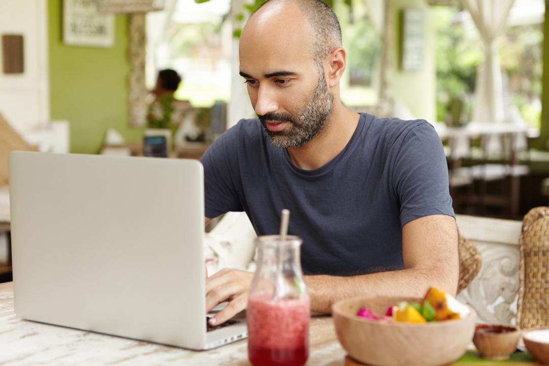 Homem negro, barbado, pesquisando o INSS para autônomo no notebook