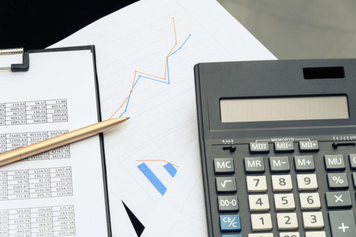 Papéis, caneta, gráficas, calculadora e planilha para calcular a bitributação