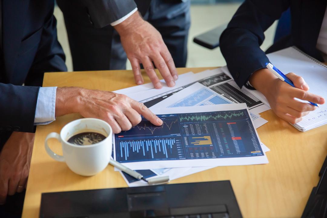 Homens analisando tabela CNAE em cima de mesa com outros papéis e itens de escritório